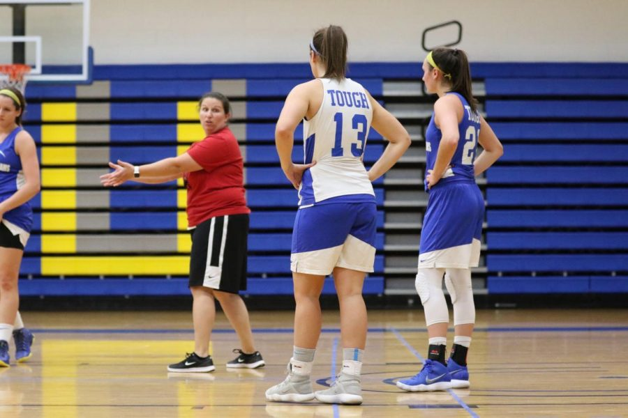 Roger Williams University women's basketball Head Coach Kelly Thompson gives helpful pointers to freshman Alyssa Grant and sophomore Sam Leone during a preseason practice.