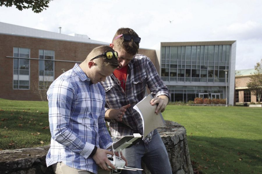 Craig Cole (left) and Justin Wilder (right) find the perfect angle to capture the Marine and Natural Sciences building, with the drone floating overhead.