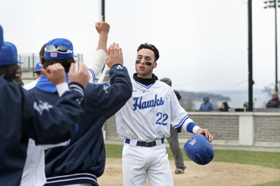 Junior Chris Bosco is greeted by his teammates after scoring a run against UMass Dartmouth on April 12.
