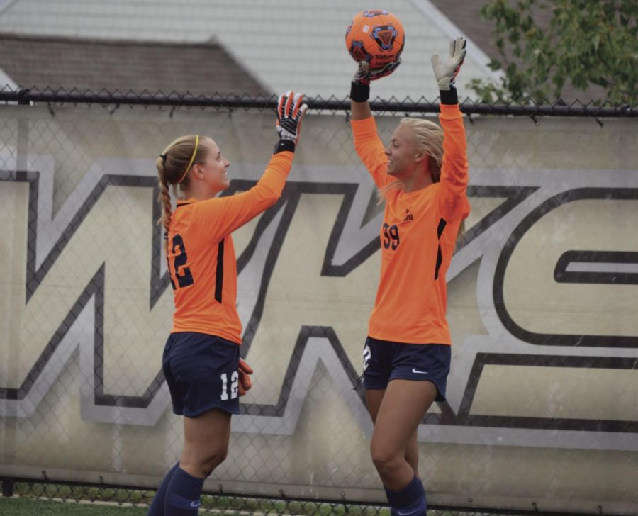 (From left to right) Goalkeepers Morgan Strassburg and Morgan McCutcheon, both freshmen, laugh when they get the ball back after kicking it over the fence while warming up at halftime during their game against Plymouth State on Saturday, Sept. 8.