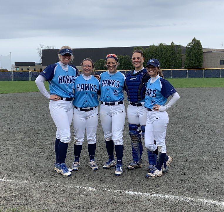 The five seniors line up for a picture after winning their doubleheader against Nichols College on April 28.