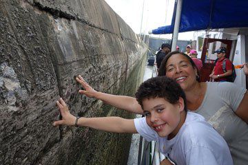 Visitors+touching+a+100-year-old+canal+wall+while+cruising+through+the+Miraflores+locks