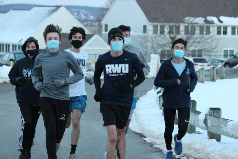 Members of the RWU Men's Track and Field Team running through campus wearing masks.