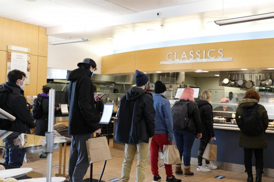 Students wait in line at Upper Commons for breakfast on Feb. 10. The dining hall is now open for all three meals for students in pods of four or less.