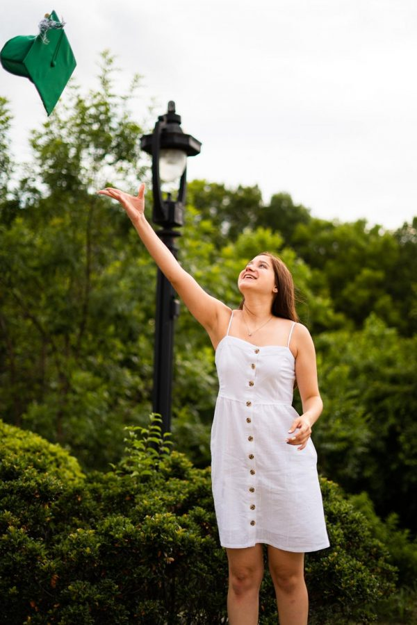 A simple white dress is a classic look for graduates. They can personalize the outfit with a necklace or wedge sandals.
