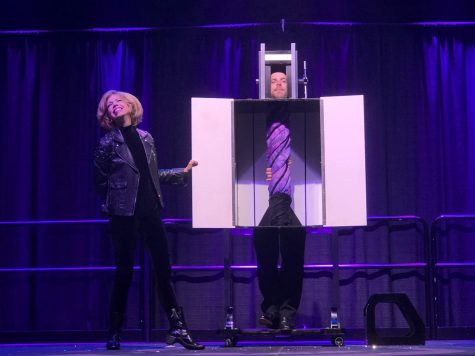 Illusionist Lyn Dillies performs a magic trick on her assistant TJ. After spinning the box around a few times, she revealed that his torso has somehow twisted.