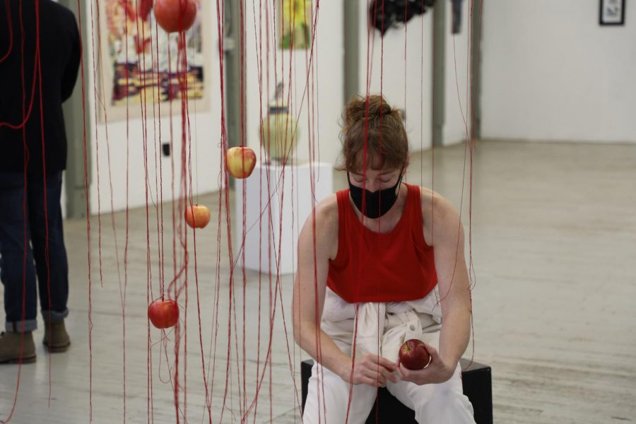 Cathy Nicoli strings apples to dangling red thread during her installation of a larger dance performance.