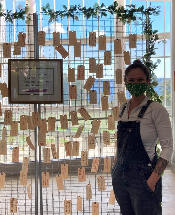 Kristen Fissell stands next to her interactive art installation in Global Heritage Hall. Each tag represents things students are proud of.